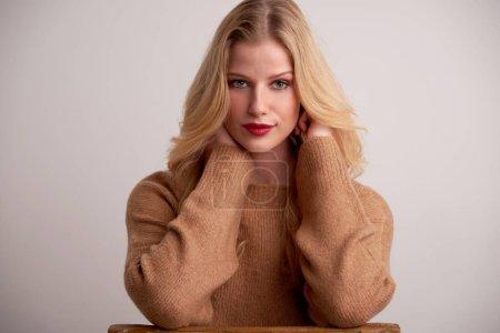 Photo pour Portrait de belle jeune femme aux cheveux longs blonds et rouge à lèvres assis sur fond isolé . - image libre de droit