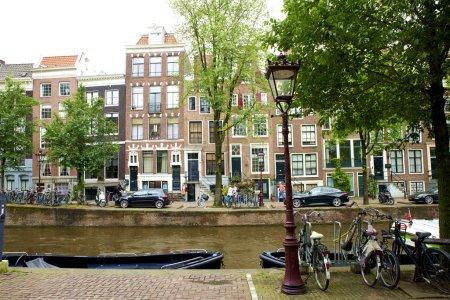 Photo pour Vue sur le canal d'Amsterdam avec bateaux et vélos . - image libre de droit