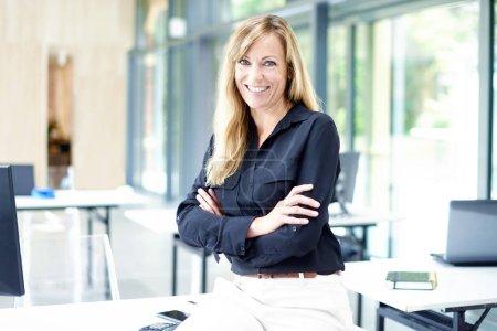 Photo pour Portrait d'une jolie femme d'affaires d'âge moyen assise avec les bras croisés dans le bureau tout en regardant la caméra et en souriant . - image libre de droit