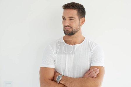 Photo pour Portrait de beau jeune homme debout avec les bras croisés sur fond blanc isolé et regardant loin . - image libre de droit