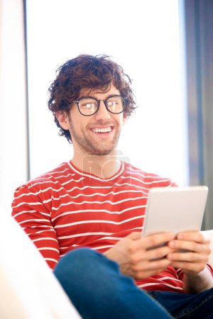 Photo for Shot of happy man using digital tablet while sitting on couch at home. - Royalty Free Image