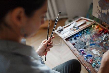 Photo pour Une jeune artiste dans son atelier tient un pinceau . - image libre de droit