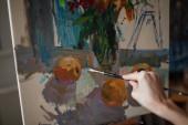 """Постер, картина, фотообои """"Молодая женщина-художник сидит в яркие студии на стуле синий и рисует картину в масле на мольберте"""""""
