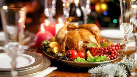 Photo pour Photo rapprochée de dinde cuite au four sur une table de fête familiale contre une cheminée en feu - image libre de droit
