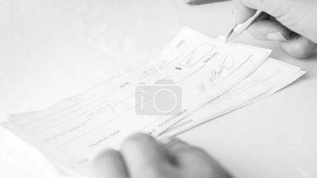Black and white image of woman writing payment bank cheque