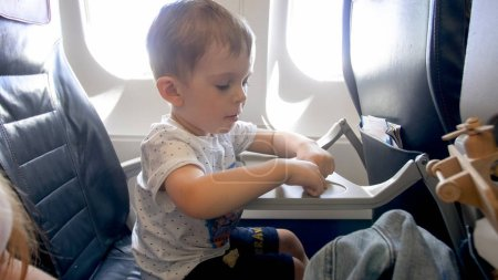 Foto de Retrato de niño pequeño sentado en el avión y jugando con juguetes - Imagen libre de derechos