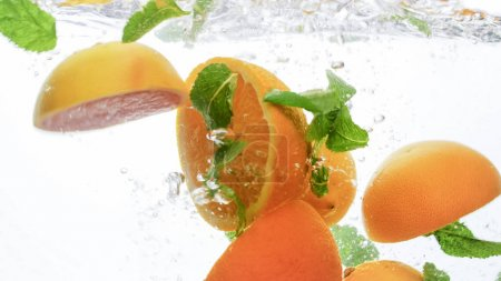 Photo for Closeup photo of fresh cut juicy orange and lots of mint leaves falling and splashing in the clear water against white background - Royalty Free Image