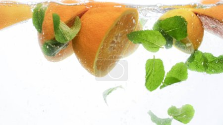 Photo for Closeup photo of cut fresh juicy oranges with mint leaves floating in clear water against white background - Royalty Free Image