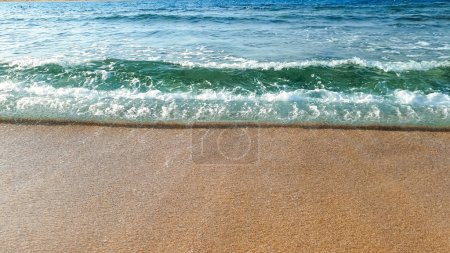 Photo for Closeup photo of calm sea waves rolling on wet sand at sea beach - Royalty Free Image