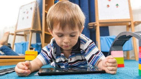 Photo pour Portrait d'un petit garçon de 4 ans allongé sur un tapis dans sa chambre et utilisant une tablette numérique . - image libre de droit
