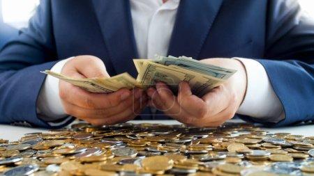 Photo pour Des mains riches tenant une pile d'argent sur un tas de pièces. Concept d'investissement financier, de croissance économique et d'épargne bancaire . - image libre de droit
