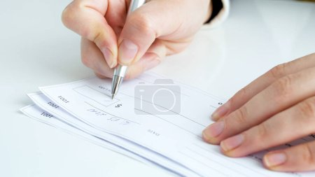 Photo for Businesswoman filling and signing banking cheque on office desk. - Royalty Free Image