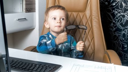 Photo for Little toddler boy holding eyeglasses sitting in office in armchair. - Royalty Free Image