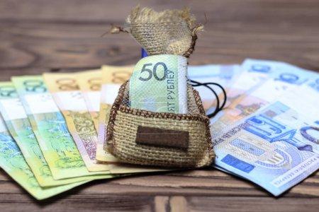 Photo pour Fond en bois. sur elle disposait l'argent biélorusse. Au centre dans le sac 50 roubles . - image libre de droit