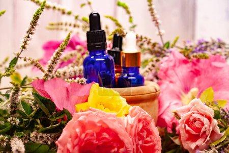 Photo pour Composition de spa avec des fleurs et des bouteilles d'huiles essentielles dans un bol en bois - image libre de droit