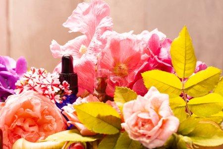 Photo pour Fleurs fraîches et les bouteilles d'huiles essentielles pour l'aromathérapie et massage - image libre de droit