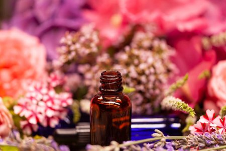 Close view of bottles of essential oils for aromatherapy on background with blurred flowers