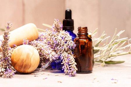 Photo pour Bouteilles d'huiles essentielles pour l'aromathérapie et pilon et le mortier de lavande - image libre de droit