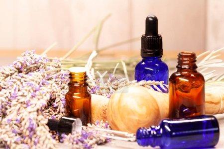 Photo pour Mortier de lavande et pilon et bouteilles d'huiles essentielles pour aromathérapie - image libre de droit