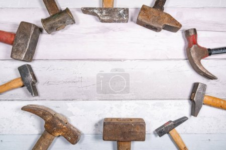 Photo for Set of different types of old hammers put in circles on a wooden background. top view with space for text. - Royalty Free Image