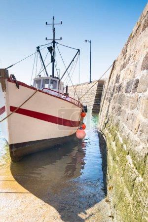 Photo pour Chalutier de pêche avec son bateau tendre sur la cale du port d'Erquy en Bretagne - image libre de droit