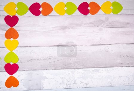 Photo for Colorful felt hearts on a background of old wooden planks resembling an old parquet floor. Concept of valentine's day and love in general. - Royalty Free Image