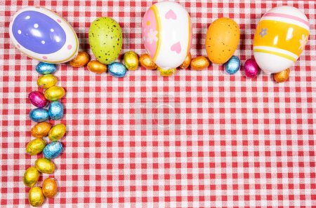 Photo for Mix of easter eggs of all colors and sizes on a background of red and white gingham fabric. Easter concept. - Royalty Free Image