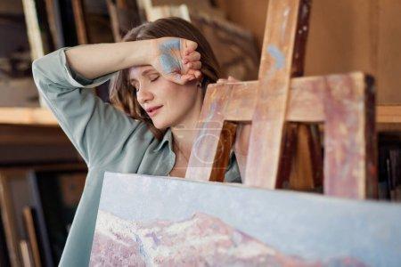 Photo pour Jeune femme peignant une palette de peinture en atelier - image libre de droit