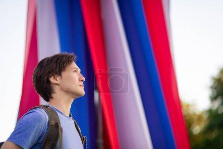 Photo pour Un jeune homme regarde vers l'avenir dans le contexte du patriote du drapeau russe. Constitution du jour du drapeau russe. Fédération de Russie. Le 12 juin. 22 août. Le 4 novembre. Citoyen. Tricolore - image libre de droit