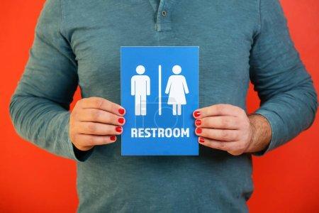 Photo pour Homme avec manucure montrant unisexe panneau de toilettes sur fond de couleur, gros plan - image libre de droit