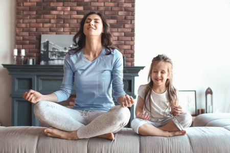Photo for Mother with little daughter meditating at home - Royalty Free Image