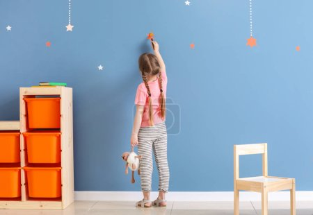 Photo for Cute little girl painting on color wall in room - Royalty Free Image