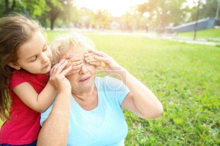 Foto de Linda niña cubriendo los ojos de su abuela en el parque - Imagen libre de derechos