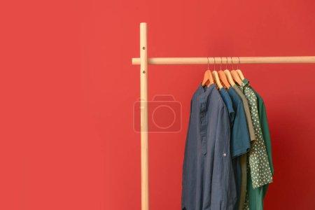 Stojak z wiszącymi ubraniami na kolorowym tle