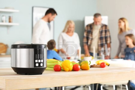 Photo pour Modern multi cooker with fresh vegetables on table in kitchen - image libre de droit