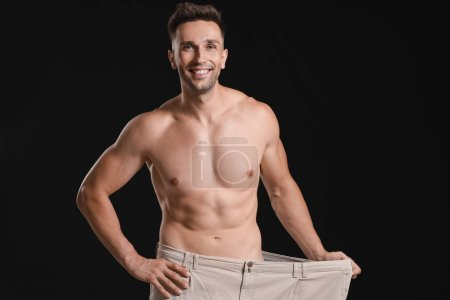 Handsome muscular man in loose pants on dark backg...