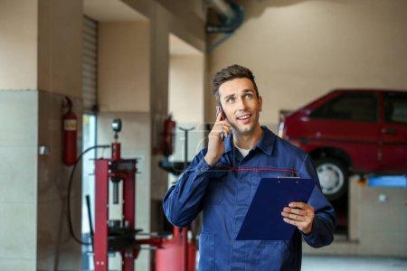 Photo pour Mécanicien parlant par téléphone dans un centre d'entretien automobile - image libre de droit
