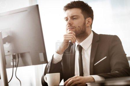 Photo pour Concept de crise commerciale. Jeune homme d'affaires assis à la table du bureau occupé à parler sur un téléphone portable résoudre un problème de travail très grave. Homme en costume à l'intérieur sur fond de fenêtre en verre. - image libre de droit