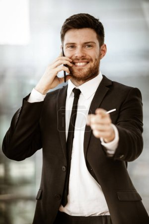Photo for Business concept. Happy smiling young businessman standing in office talking on a cell phone getting good news about his work and pointing with finger. Man in suit indoors on glass window background. - Royalty Free Image