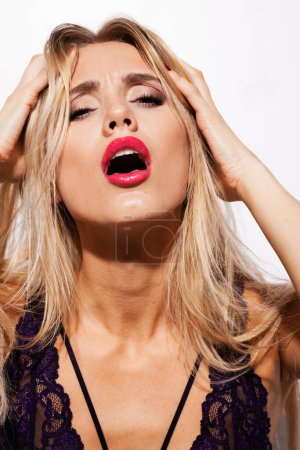 Photo for Emotions and feelings concept - beautiful blond lady portrait in sexy lingerie while getting an orgasm on white background. Woman shouts in ecstasy in bright light. - Royalty Free Image