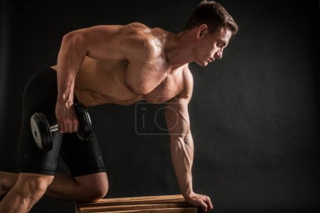 Photo for Fitness in gym, sport and healthy lifestyle concept. Handsome athletic man showing his trained body on dark background. Bodybuilder male model training biceps muscles with dumbbell. - Royalty Free Image