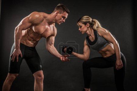 Foto de Fitness en gimnasio, deporte y estilo de vida saludable. Un par de hombres y mujeres atléticos mostrando sus cuerpos entrenados sobre un fondo oscuro. Dos modelos de culturistas de pie y demostrando músculos apretados. - Imagen libre de derechos