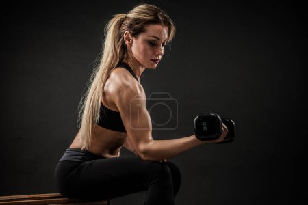 Photo for Fitness in gym, sport and healthy lifestyle concept. Beautiful athletic woman showing her trained body on dark background. Bodybuilder female model training biceps muscles with dumbbell. - Royalty Free Image