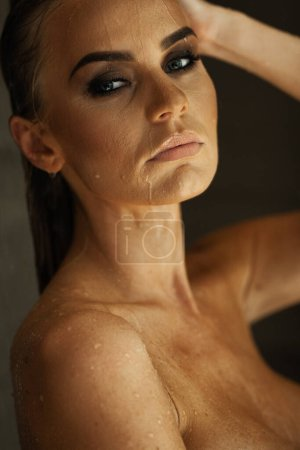 Photo for Relaxation and spa concept. Portrait of a sexy fashionable lady in a black swimsuit. Woman with wet hair and makeup poses in water in swimming pool in natural sunlight. - Royalty Free Image