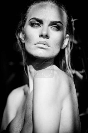 Photo pour Concept de détente et spa. Portrait rapproché d'une dame sexy à la mode en maillot de bain noir. Femme aux cheveux mouillés et maquillage pose dans la piscine à la lumière naturelle du soleil. Noir et blanc, monochrome. - image libre de droit