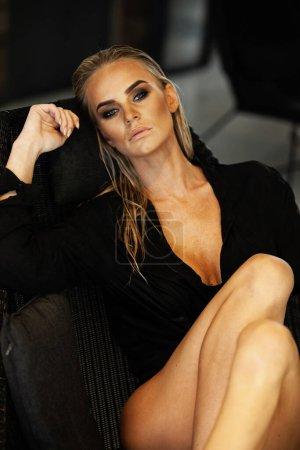 Photo pour Concept de détente et spa. Portrait d'une dame sexy à la mode en maillot de bain noir. Femme aux cheveux mouillés et maquillage pose dans la chaise près de la piscine à la lumière naturelle. - image libre de droit