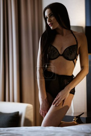 Photo for Beauty of woman body and lingerie concept. Beautiful brunette female fashion model in sexy black underwear poses in luxury hotel room. Young girl kneels on a bed in bedroom wearing bra and panties. - Royalty Free Image