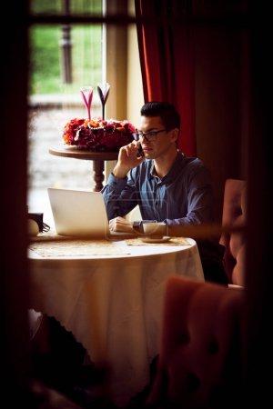Photo pour Concept de style de vie communautaire LGBTQ. Jeune homme homosexuel assis à la table dans un café de la ville à l'ancienne. Beau gay homme d'affaires parle sur un téléphone tout en ayant une pause au déjeuner. - image libre de droit
