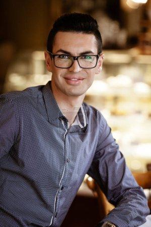 Photo pour Concept de style de vie communautaire LGBTQ. Jeune homme homosexuel assis à la table dans un café de la ville à l'ancienne. beau souriant gay mâle homme d'affaires pose tout en ayant une pause au déjeuner. - image libre de droit