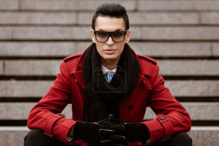 Photo for LGBTQ community lifestyle concept. Young homosexual man sits on a stairs. Handsome fashionable gay male model poses in cityscape outdoors. Wears red coat, gloves, sunglasses and black scarf. - Royalty Free Image